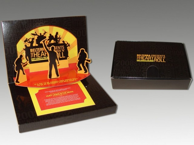 "Huey Lewis New Year's Eve Invitation 1 / 1 Code: 6107-1311 Services: Tradeshows & Events, Travel & Entertainment Client: SK+G for Belterra Casino Resort Belterra Casino Resort used this box to invite VIP members to an exclusive New Year's Eve event featuring a concert by iconic 80's band, Huey Lewis & The News. The inside of this elaborate box featured a pop-up silhouette of the band and a sound chip of their hit ""Heart of Rock and Roll"" immediately played when the box was opened."